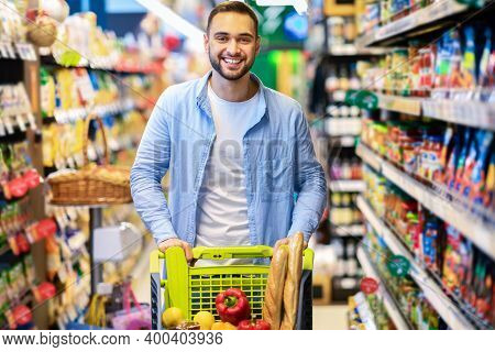 Groceries Shopping. Smiling Happy Bearded Guy Standing With Shopping Cart In The Aisle In Hypermarke