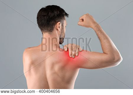 Back View Of Topless Man Suffering From Shoulder Pain Injury, Rubbing Sore Zone Over Grey Studio Bac