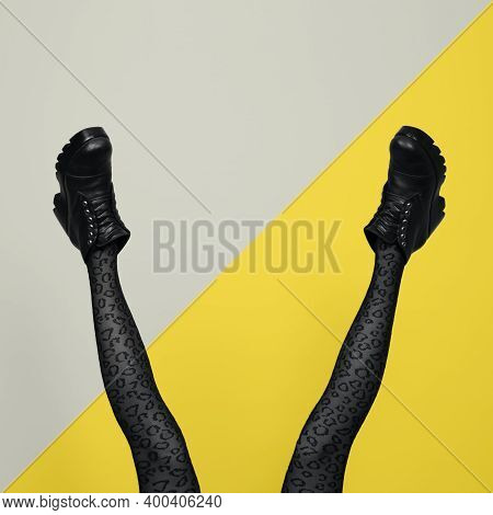 New Gray Female Boots On Long Slender Woman Legs In Gray Tights Isolated On Yellow And Gray Backgrou