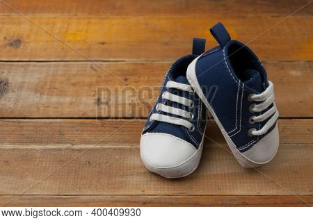 Baby boy blue sneakers standing on the woooden table