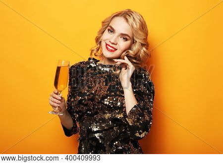 Young stylish woman drinking champagne, celebrating new year, wearing evening dress. Happy New Year to you. One young and beautiful woman dancing with glass of champagne and smiling.
