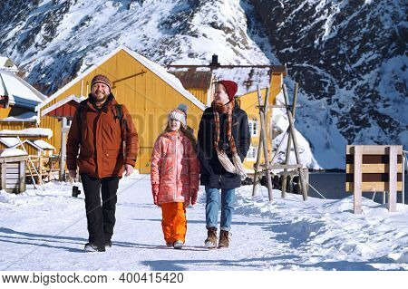 Happy Family Trip To Lofoten Islands. Dad And Two Daughters  At The Nusfjord. Norway