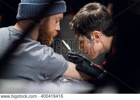 A Tattoo Artist With Short Hair And Piercings Is Preparing To Get A Tattoo On A Mans Arm In A Tattoo