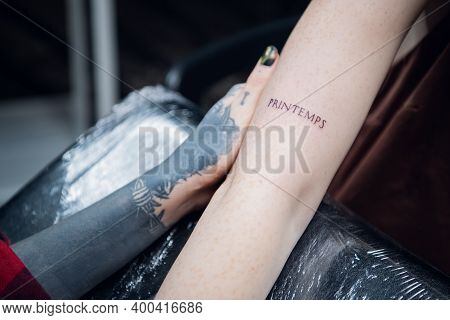 The Hand Of A Tattoo Artist A Girl With Tattoos And A Newly Made Tattoo In The Form Of A Word, On Th
