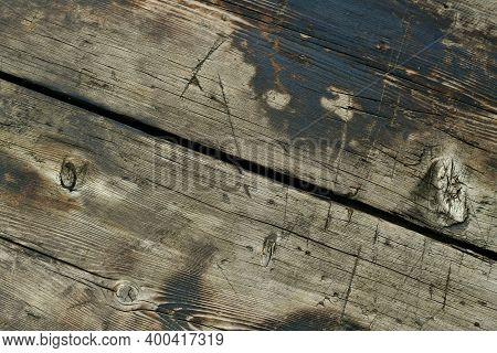 The Background Is Wooden, A Fragment Of Two Boards, Diagonal From Top To Bottom, With A Gap Exactly