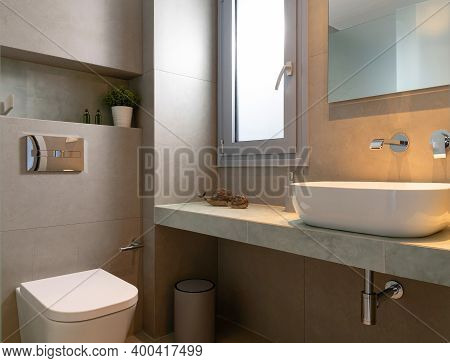 Modern Style Interior Of Small Bathroom Tiled Gray Stone With Window, Vessel Bowl Sink, Mirror Back