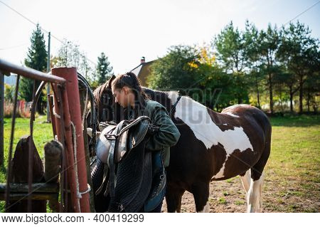 After A Ride, The Jockey Unsaddles The Horse Next To The Fence At The Ranch.