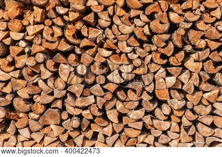 Pile Stacked Natural Wood Logs. Background Of A Wall Made Of Firewood. Traditional Way To Prepare Fo