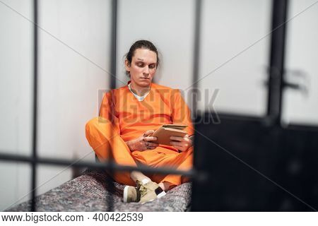 Young Criminal In A Solitary Cell Reads A Book Sitting On A Bunk In An Orange Prison Uniform. Photo