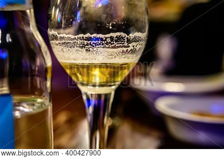 Close-up Of An Unfinished Glass Of Beer On A Table In A Cafe On A Blurred Background.