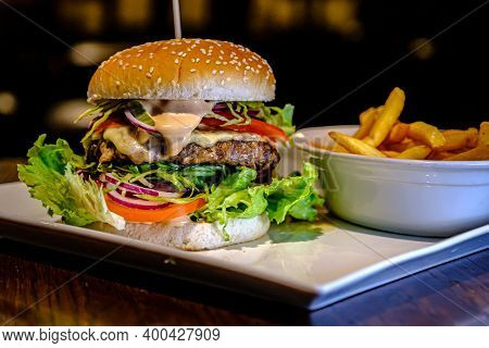 Delicious Juicy Burger With Herbs And Fries On The Table. Cheese Burger With Beef, Patty, Tomato And