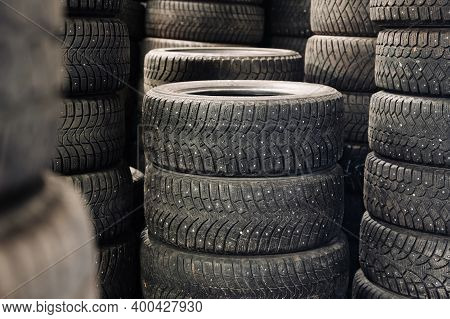 A Pile Of Used Spiked Tires And Treads In A Car Warehouse. Stack Of Old Tires.