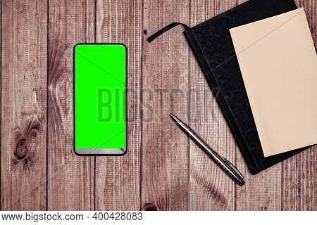 Smartphone With Green Screen, Notepad And Pen On Wood Background.