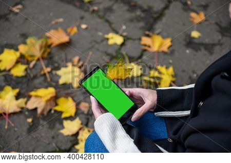 Woman Holding A Smartphone In Hands With A Green Screen, Hand Holding A Mobile Smartphone With A Gre
