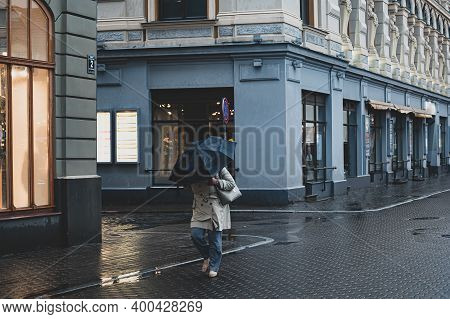 A Single Woman Walks In The Old City With An Umbrella In The Rain And Wind.