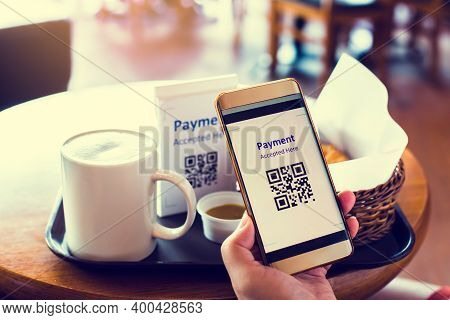 Customer Hand Using Smart Phone To Scan Qr Code Tag With Blur Coffee And Bread In Coffee Shop Or Res