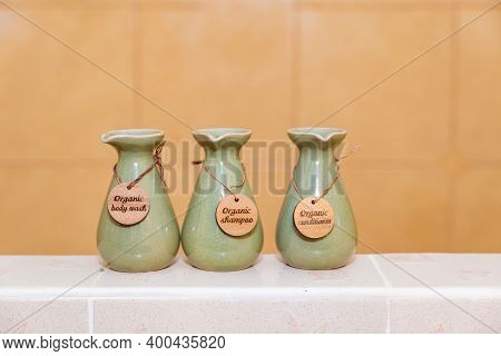 Green Ceramic Bottles Of Shampoo, Conditioner And Body Soap On The Background Of The Bathroom, Woode