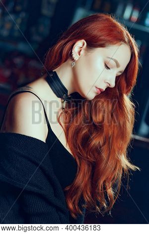 Indoor portrait of stylish redhead young woman, elegant serious girl with red long hair posing indoors