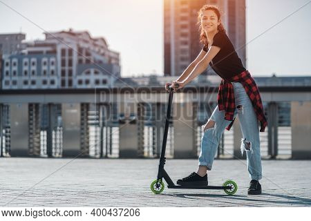Young Teenager In Sneaker On Modern Extreme Stunt Kick Scooter In City