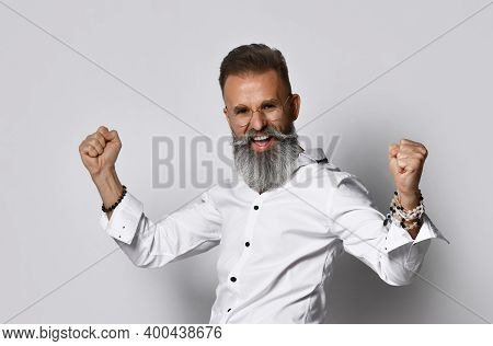 Excited Stylish Mature Grey-haired Bearded Hipster Man In Eyewear Screaming Yes Raising Fists Celebr