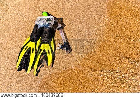 Snorkeling Equipment Set Snorkel Mask Fins Lie On Golden Sand By The Seashore