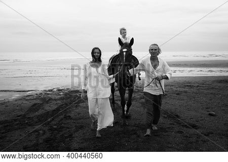 Monochrome. Little Pretty Girl On A Horse. Parents Leading Horse By Its Reins On The Beach. Horse Ri