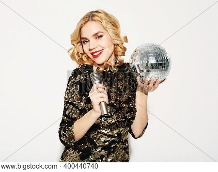 Christmas, celebration party, holiday concept. Young woman in evening dress holding microphone and disco ball. Brighrt make up and Wavy hairstyle.