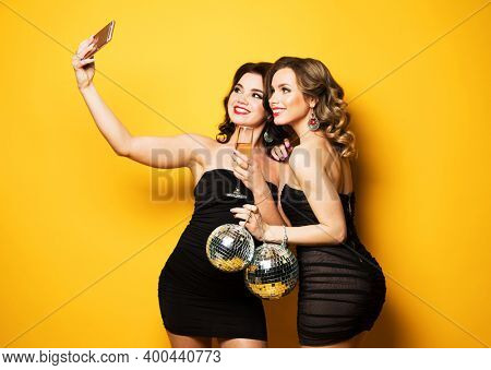 two fashionable young women wearing black cocktail dresses holding disco balls and make a selfie.