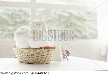 Towel Placed On Basket, White Table Top, Bottle Of Liquid Soap, Spa Set For Bathing In The Bathroom,