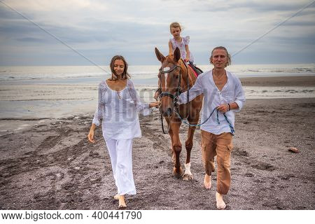 Little Pretty Girl On A Horse. Husband And Wife Leading Horse By Its Reins On The Beach. Horse Ridin