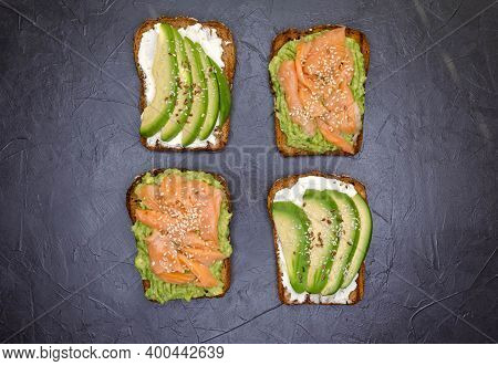 Tasty Open Sandwich With Rye Bread, Avocado, Smoked Salmon On Dark Concrete Background. Set Of Vario