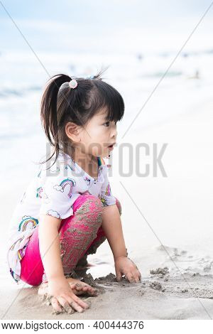 Portrait Of Asian Girl Sitting By The Beach. Children Are Playing In The Sand. Learning Through Five