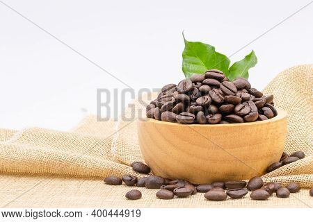 Coffee Beans Roasted In A Wooden Bowl On Sackcloth Over White Background.