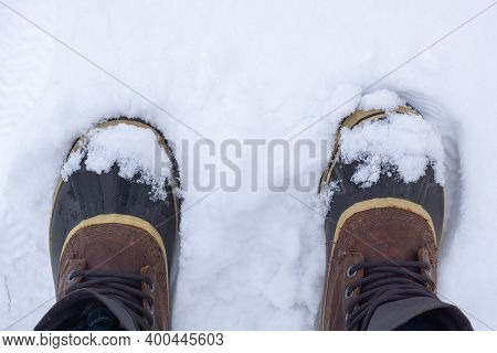 Top View Of Anonymous Traveler In Warm Boots Standing On White Snow On Winter Day.