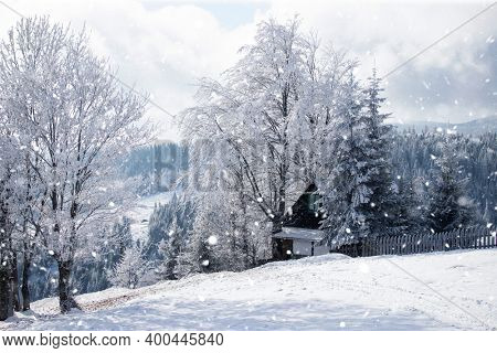 Fantastic winter landscape with wooden house in snowy mountains. Christmas holiday and winter vacations concept