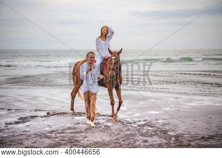 Horse Riding By The Sea. Woman On A Brown Horse. Man Leading Horse By Its Reins. Love To Animals. Hu