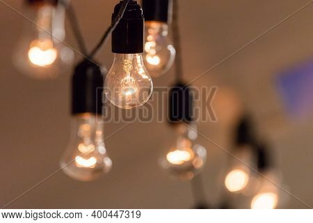 Close Up View Of Vintage Decorative Light Lamp Bulb Glowing On The Ceiling Indoors. Transparent Lamp