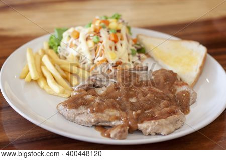 Pork Chop And Sauce Served With Toast, French Fries And Salad In White Plate In Wooden Table.