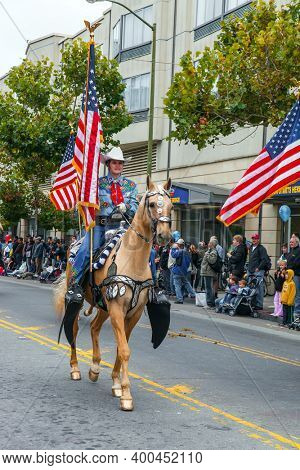 SAN FRANCISCO, USA - OCTOBER 11, 2009: Equestrian parade in honor of the United States national holiday. Columbus Day celebration. Dressy riders in cowboy hats carry US flags