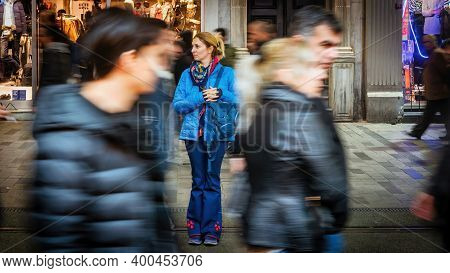 Istanbul, Turkey - November 2019: Woman Standing Alone Among Crowd Of People In Taksim Square Istikl