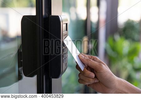 Young Woman Using Rfid Tag Key, Fingerprint And Access Control  To Open The Door In A Office Buildin