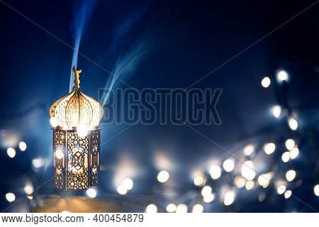 Ornamental Arabic lantern with burning candle glowing at night and glittering golden bokeh lights. Festive greeting card for Muslim holy month Ramadan Kareem.