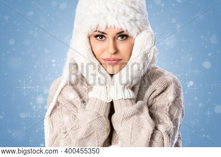 Young Beautiful Woman Wearing Winter Hat And Mittens Over Blue Background With Snowflakes