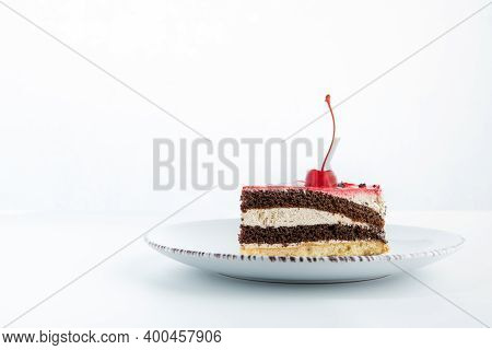 Chocolate And Vanilla Cake Cut Into Pieces. There Is Cherry On Top. Side View To Piece Of Cake On Wh