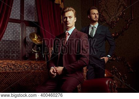 Portrait of two handsome young men in elegant classic suits posing in a luxury apartments with classic interior. Men's beauty, fashion.
