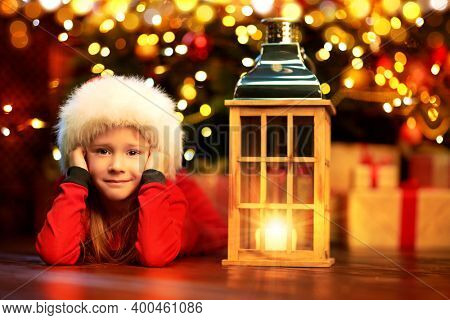 Dreamy little girl lying on a floor by a burning lantern and a Christmas tree at home. Merry Christmas and Happy new Year!