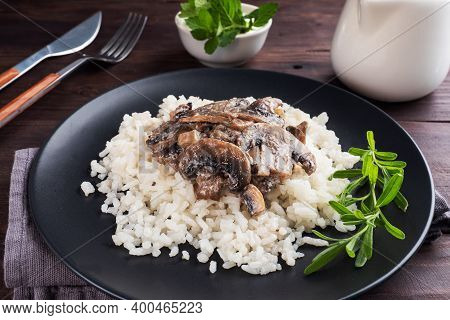 Risotto With Mushrooms On A Black Plate. Boiled White Rice With Champignons In Cream Sauce. Dark Woo
