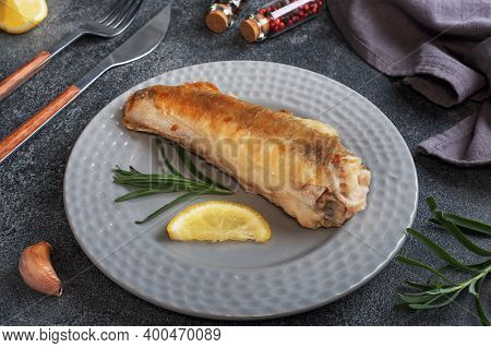 Fried Fish Hake Pollock And Slices Of Fresh Lemon. Dark Concrete Background. Copy Space.