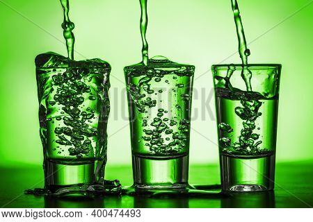 Vodka Shots Background. Green Transparent Vodka Shots. Pouring Vodka Into Glass. Green Bubble Alcoho