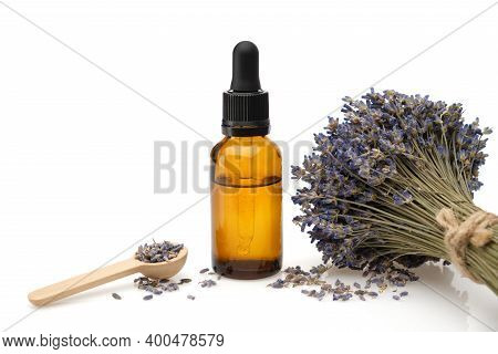 Dropper Bottle Of Lavender Essential Oil Or Aromatic Flower Water, Wooden Spoon Of Dry Petals And Bu